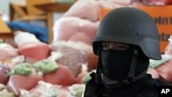 A policeman stands guard near bags of methamphetamine pills in Ayutthaya province, north of Bangkok, Thailand, June 24, 2011.