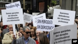 Journalist hold placards reading 'We are guarantors of the constitutional right to information' and 'There is no democracy without journalism' during a demonstration to mark the World Press Freedom Day on May 03, 2012 in Madrid. (AFP)