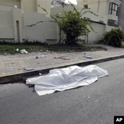 The body of a person killed during clashes between demonstrators and police lies in the street in Manama, February 17, 2011