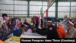 Sekdaprov Jawa Timur memakaikan face shield kepada para pedagang dan pengunjung Pasar Oro-oro Dowo, Malang. (Foto: Humas Pemprov Jawa Timur)