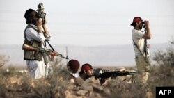 Binh sĩ của phe nổi dậy tuần tra phía nam sa mạc của thị trấn Chakchuk trong Vùng núi phía Tây, cách thủ đô Tripoli khoảng 160 km về hướng tây nam, ngày 4/6/2011