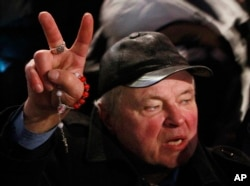 A supporter of the government holds a rosary and shows a victory sign during the demonstration organized by the ruling Polish party Law and Justice in Warsaw, Tuesday, Dec. 13, 2016.