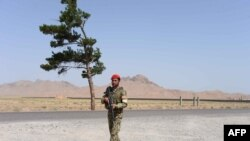 An Afghan National Army soldier walks on the outskirts of Herat on June 29, 2015.