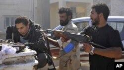 ພວກນັກລົບຝ່າຍປະຕິວັດ ຈັບຜູ້ຕ້ອງສົງໄສຄົນນຶ່ງ ວ່າເປັນກຳລັງ ທີ່ຈົງຮັກພັກດີຕໍ່ມວມມາກາດດາຟີ (ຊ້າຍ) ໃນເຂດໃຈກາງເມືອງ Sirte (12 ຕຸລາ 2011)