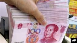 银行出纳员在货币兑换处清点人民币。(资料照片)