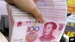 Penghitungan mata uang yuan di sebuah tempat pertukaran mata uang di Hong Kong.