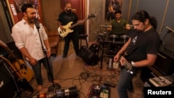 FILE - Guitarist Khurram Waqar, right; vocalist Umair Jaswal, left; bass guitarist Rahail Siddiqui; and drummer Asfendyar Ahmad of the rock band Qayaas, shown rehearsing last April in Islamabad,say the security situation has hampered Pakistan's music scene.