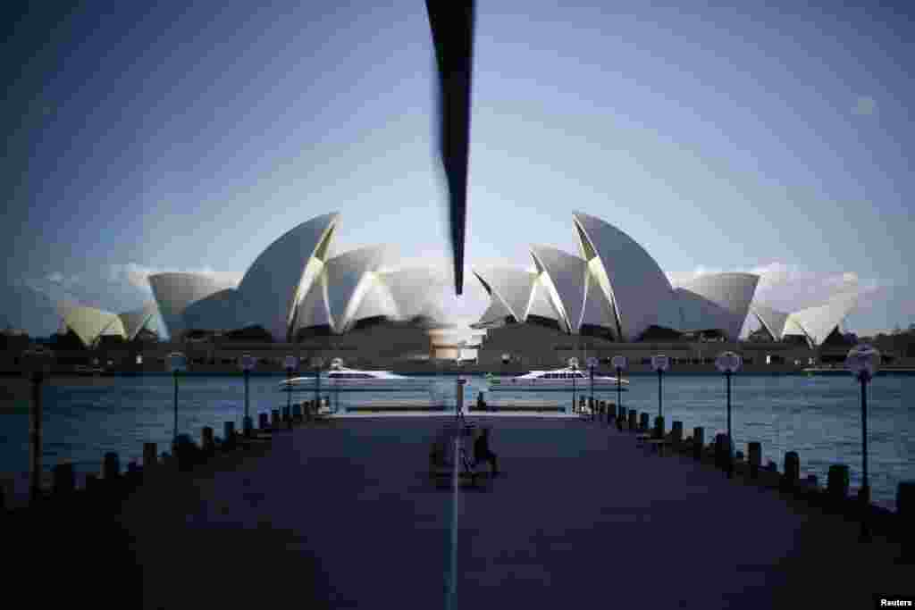 Gedung Opera Sydney (kanan) tercermin dalam jendela sebuah hotel di kota Sydney, Australia.