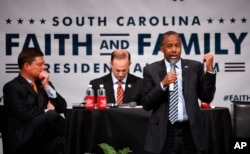 Ben Carson, accompanied by South Carolina Attorney General Alan Wilson, left, and Dr. Oran Smith of the Palmetto Family Council, speaks during the Faith and Family Presidential Forum at Bob Jones University in Greenville, S.C., Feb. 12, 2016.
