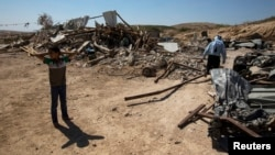 Khader Abu al-Kian (R) and his son walk among the rubble of their family's home which was demolished by Israeli authorities in the village of Atir, August 6, 2013.