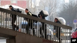 Migrant workers carrying their belongings walk up an overpass near the railway station upon arriving in Beijing, 02 March 2010