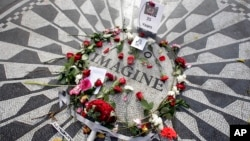Flowers adorn the Imagine mosaic in remembrance of John Lennon, in the Strawberry Fields section of New York's Central Park, Tuesday, Dec. 8, 2015. Thirty-five years ago, Mark David Chapman shot and killed the former the Beatle. (AP Photo/Richard Drew)