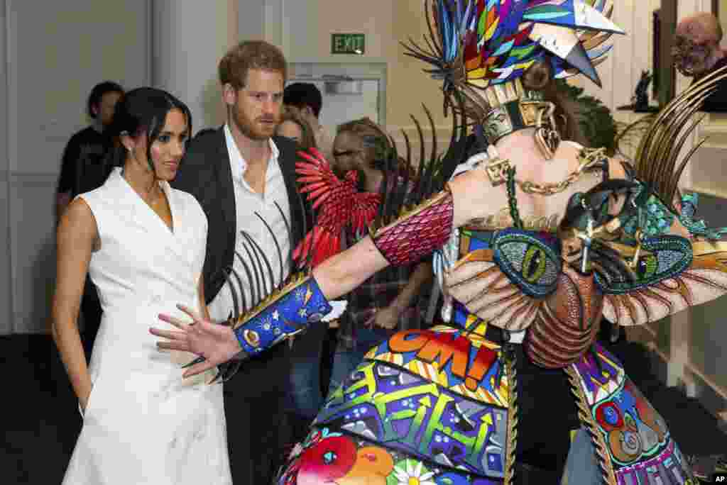 Britain's Prince Harry and Meghan, Duchess of Sussex, meet actors in costume during a visit to Courtenay Creative in Wellington, New Zealand.