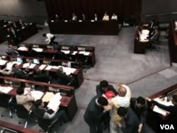 香港政務司司長林鄭月娥在立法會簡介港府第一階段政改諮詢報告,人民力量陳偉業議員上前抗議她「一錘定音」假諮詢,被保安人員帶離會議室。