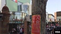 属于中国官方天主教爱国会系统的天津西开总堂在庭院内贴出的招收新教徒的学习班通知,院外是喧嚣的商业区。(2017年资料照)