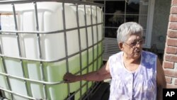 Vickie Yorba, 94, stands next to a water tank in front of her home in East Porterville, California, Sept. 15, 2014. Her water well is one of 290 in the area that ran dry in the state's historic drought. (AP Photo/Scott Smith)