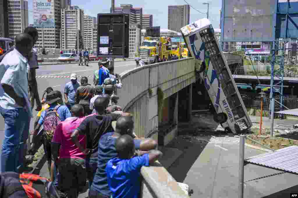 Onlookers gather on Queen Elizabeth bridge to look at a public transport bus that drove over the side of the bridge in Johannesburg, South Africa. No fatal injuries were reported and the bus driver had minor injuries.