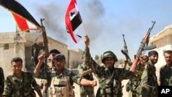 叙利亚战士挥舞叙利亚国旗,庆祝占领叙利亚哈马省一个地区。(2015年10月11日)