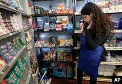 En esta foto del 17 de mayo de 2018, Miriam Zouzounis revisa una selección de productos de tabaco mientras es entrevistada en Ted's Market, la tienda de su familia, en San Francisco.