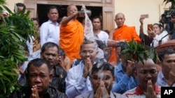 Meach Sovannara, center, a former spokesman of the opposition Cambodia National Rescue Party, receives holy water from a Buddhist monk on the outskirts of Phnom Penh, Cambodia, Tuesday, Aug. 28, 2018. Fourteen Cambodian opposition activists were freed Tue