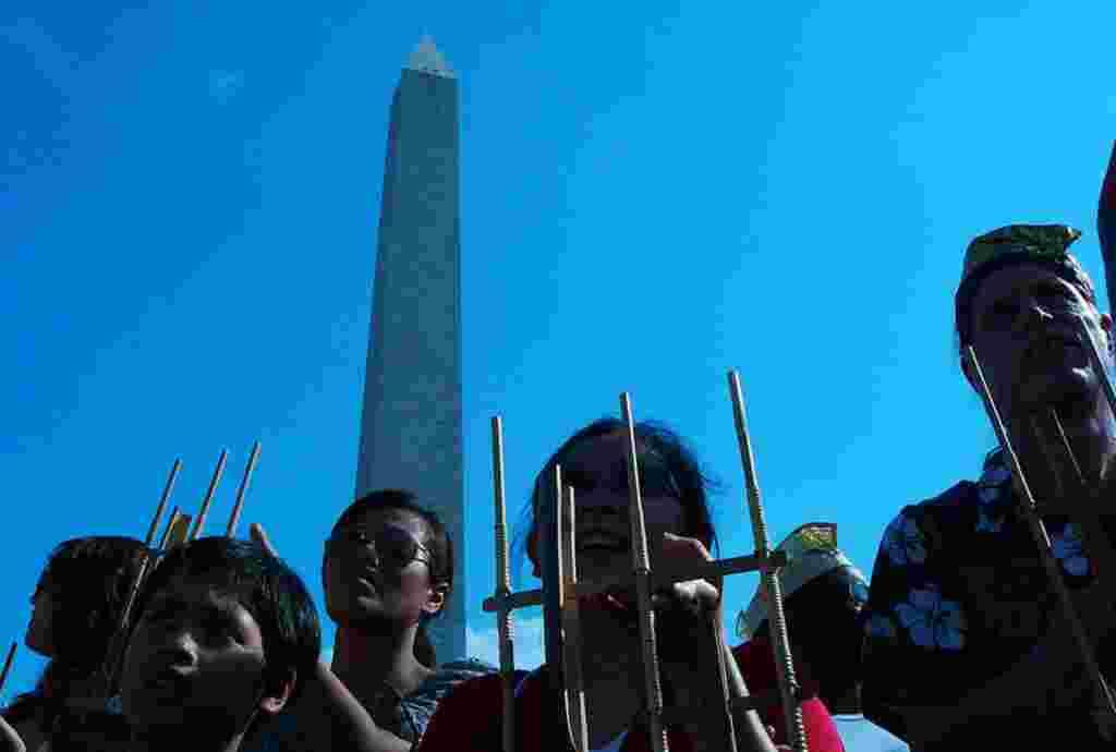 Warga Indonesia de Amerika dan warga setempat berdiri berdampingan memainkan anglung dalam acara ini (foto: Ratnasari Dewi-VOA)