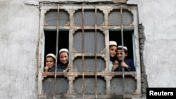 Afghan students from a religious school look on from a window of their school in Kabul, Afghanistan, Oct. 5, 2016.