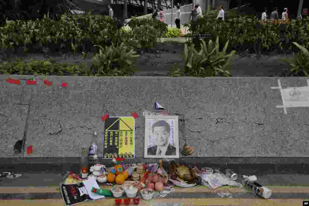 Offerings are placed in front of an altar set up by pro-democracy demonstrators to mark the symbolic death of Hong Kong Chief Executive Leung Chun-ying, near government headquarters in Hong Kong, Oct. 16, 2014.