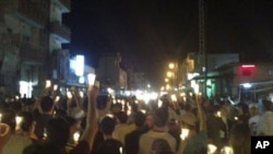 In this citizen journalism image made on a mobile phone Tuesday May 10, 2011 and acquired by the AP, Syrian anti-government protesters carry candles during a rally in the northeastern city of Qamishli, Syria.