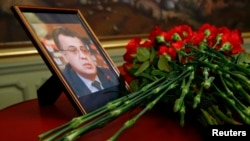 Flowers are placed near a portrait of assassinated Russian ambassador to Turkey Andrei Karlov during a meeting of Russian Foreign Minister Sergei Lavrov with his Turkish counterpart Mevlut Cavusoglu in Moscow, Russia, Dec. 20, 2016.