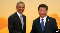ປະທານນາທິບໍດີ Barack Obama (ຊ້າຍ) ສຳພັດມືກັບ ປະທານປະເທດ ຈີນ ທ່ານ Xi Jinping (ຂວາ)