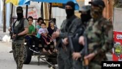 Palestinska deca gledaju u militante Islamskog džihada koji stražare nakon primirja između Izraela i Hamasa, u Gazi, 21. maja 2021. (Foto: Rojters, Ibrahim Abu Mustafa)