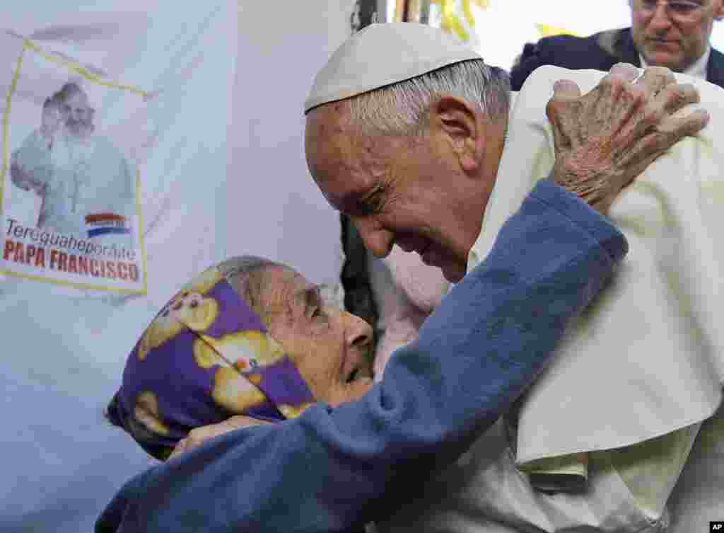 Pope Francis is greeted by an elderly woman during his visit to the Banado Norte neighborhood in Asuncion, Paraguay.