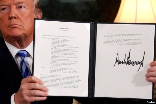 FILE - U.S. President Donald Trump holds up a proclamation declaring his intention to withdraw from the JCPOA Iran nuclear agreement after signing it in the Diplomatic Room at the White House in Washington, May 8, 2018.