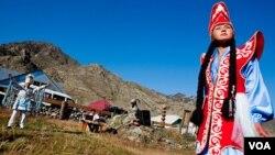 Một phụ nữ trình diễn trang phục truyền thống của người địa phương tại trung tâm văn hóa Chui Oozi, phía sau cô là ca sĩ Bolot Byiryshev, một trong những ca sĩ giọng hầu hay nhất của Altai, vừa trình bày một khúc hùng ca