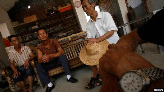 Một bệnh nhân bị ung thư dạ dày (trái) đang nói chuyện với bạn bè trong làng Shangba thuộc tỉnh Quảng Đông