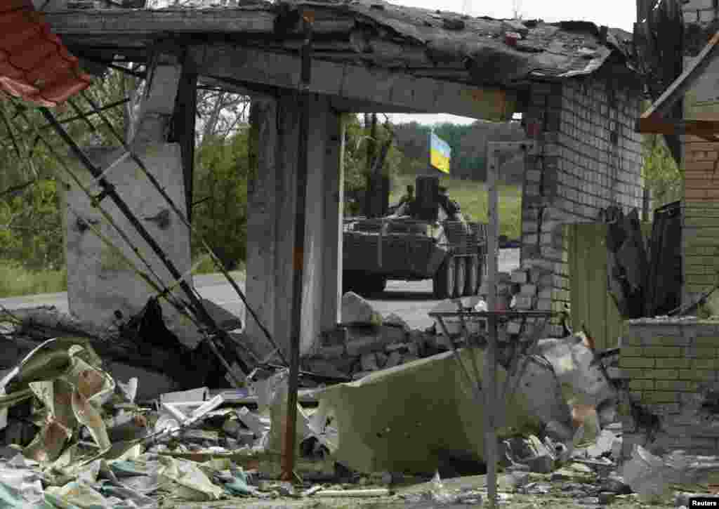 A Ukrainian army military armored vehicle is seen through a ruined building on the outskirts of Slovyansk, Aug. 5, 2014.