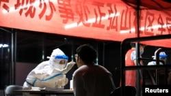 一名醫護人員在給一名鄭州市民做新冠病毒核酸檢測。 (2021年8月2日)