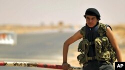 一名利比亞反政府士兵看守一處石油設施進口。