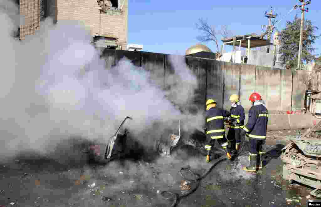 Firefighters hose down a destroyed vehicle at the site of a suicide bomb attack in Kirkuk, Iraq, Feb. 3, 2013.
