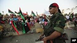 ນັກລົບຕໍ່ຕ້ານ Gadhafi ຄົນນຶ່ງຢືນຍາມທີ່ຈະຕຸລັດວິລະຊົນຫຼື Martyrs Square ທີ່ນະຄອນຫຼວງຕຣີໂປລີ (2 ກັນຍາ 2011)