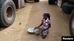 在马里北部的加奥,一个女孩子在捡拾一个人道救援车队不小心洒到地上的米
