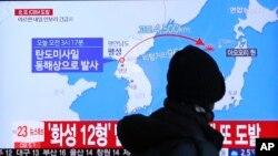 一名市民行經首爾火車站觀看電視播放北韓導彈發射資料照。