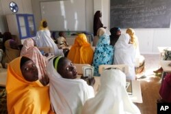 FILE - Children displaced by Boko Haram receive lessons in a school in Maiduguri, Nigeria, Dec. 7, 2015.