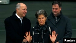 FILE - Former hostage Claudia Priest gestures after being greeted by French Foreign Minister Laurent Fabius, left, and her son upon her arrival at the Villacoublay military airport, near Paris, Jan. 25, 2015.