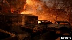 Los fuertes vientos de San Ana soplan las brazas cerca de un auto en llamas cerca de Santa Paula, California.