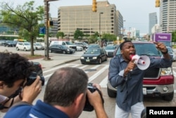 FILE - A demonstrator blocks traffic as protests moved into the street on the first day of pretrial motions for six police officers charged in connection with the death of Freddie Gray in Baltimore, Maryland, Sept. 2, 2015.