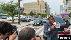 Un manifestant bloque la circulation pendant que d'autres protestaires avancent lors d'une manifestation pour Freddie Gray, jeune noir mort alors qu'il était en détention par police, à Baltimore, Maryland, 2 septembre 2015.