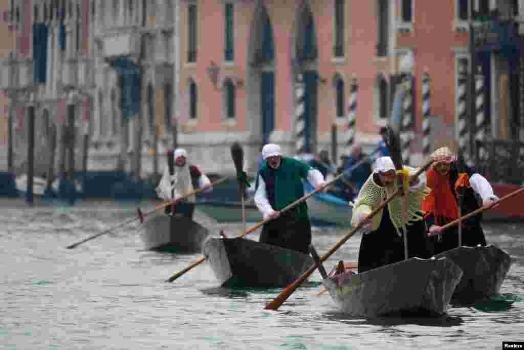 បុរសៗស្លៀកពាក់ក្នុងសម្លៀកបំពាក់ស្រ្តីវ័យចំណាស់ ដែលតាមចំណេរថា យកកាដូមកឲ្យក្មេងៗ អុំទូកតាមព្រែកជីក Grand Canal ក្នុងក្រុង Venice ប្រទេសអ៊ីតាលី អំឡុងពេលពិធីបុណ្យ Epiphany។