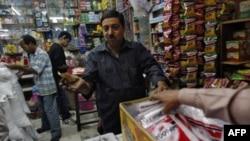 Ashwani Dang, chủ 1 gian hàng, trả giá với người mua tại chợ Karol Bagh ở New Delhi, 24/11/2011