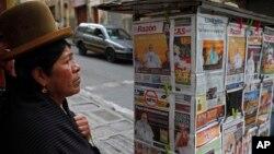 Una mujer aymara estudia la oferta de periódicos en Bolivia. El fisco cerró al decano de la prensa, El Diario.